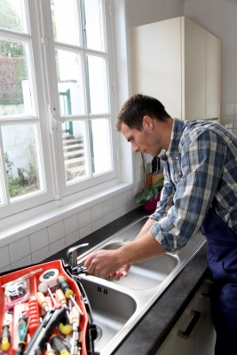 Plumbing contractor installs a new kitchen sink
